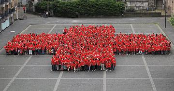 Eine grosse Menschenmenge bildet das rote Kreuz des DRK nach